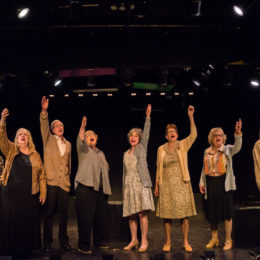 A group of actors onstage at HB Studio, all of them have one arm stretched upwards