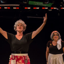 Two actors on stage at HB Studio, one with arms outstretched.