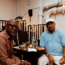Two men at HB Studio enjoying food and drink