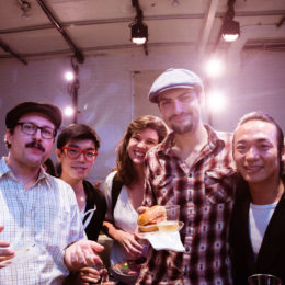 A group of people at HB Studio eating and having fun. Two men wear hats, two men wear glasses but not the same men.