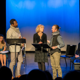 Three actors centre stage perform a reading in front of two other actors