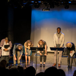 Actors bowing on stage after a reading