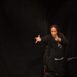 A woman, dressed in black, makes gestures with her hands