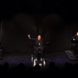 Three people on stage participate in a performance.