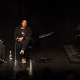 Two women sit with a water bottle between them, their legs crossed. The woman on the left has papers and glasses and on the right? Her hands are clasped. The male guitarist to the far right of stage, blinks.