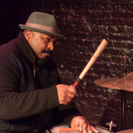 A man in a jacket plays the drums. His hat has a great brown stripe wrapped around it. He is focused, seemingly on something in the distance, but his aim for his cymbal is true and you can almost here the crash.