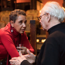 A woman leans over a banister, holding her plastic cup of wine, and looking with earnest eyes at the man speaking to her. The man, wearing glasses and turtle neck, speaks to her and uses his hands to gesture towards a point.