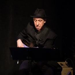 Elliott Sharp plays the guitar. He looks at his music stand, reading the notes and plucking them out on his instrument.