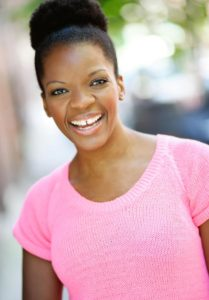 A woman in a pink sweater-shirt smiles for the camera